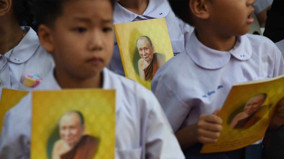 Children hold booklets carrying pictures of Thailand's most senior Buddhist monk, the late Supreme Patriarch Somdet Phra Nyanasamvara