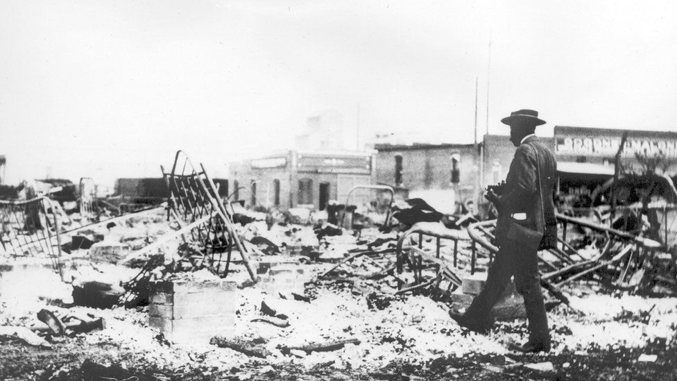 Photograph of an African-American man with a camera looking at the skeletons of iron beds which rise above the ashes of a burned-out block after the Tulsa Race Riot, Tulsa, Oklahoma, 1921