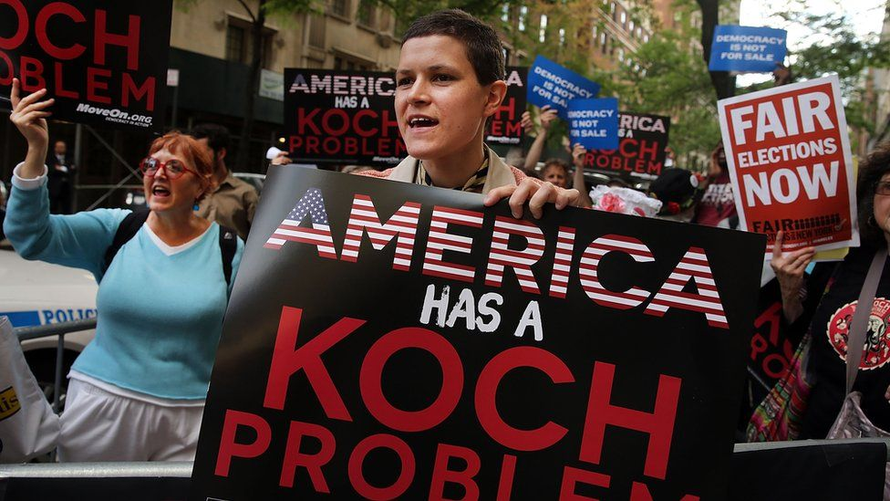 "A woman holds up a sign reading ""America has a Koch problem"""