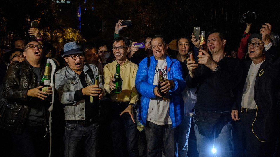 Pro-democracy protesters open champagne bottles to the news that unpopular chief executive Leung Chun-Ying said he would not run for office again in the March vote, during a rally outside his residence in Hong Kong on December 11, 2016,