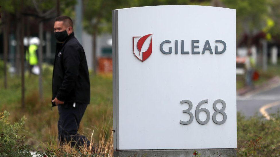 Man near a sign in front of the Gilead Sciences headquarters