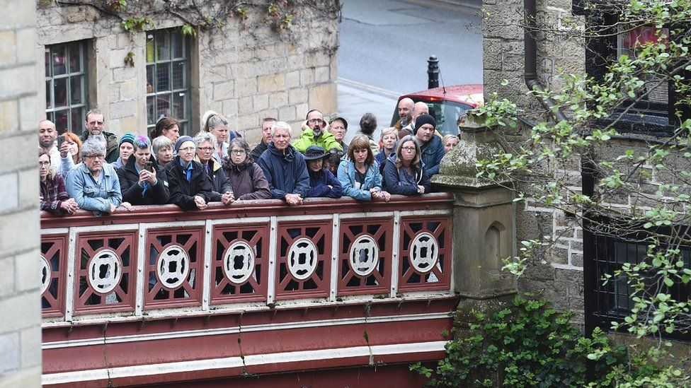 People line a bridge to listen to politicians speak ahead of the 2017 general election