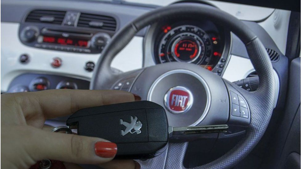 A woman holds a Peugeot car key in front of a Fiat steering wheel