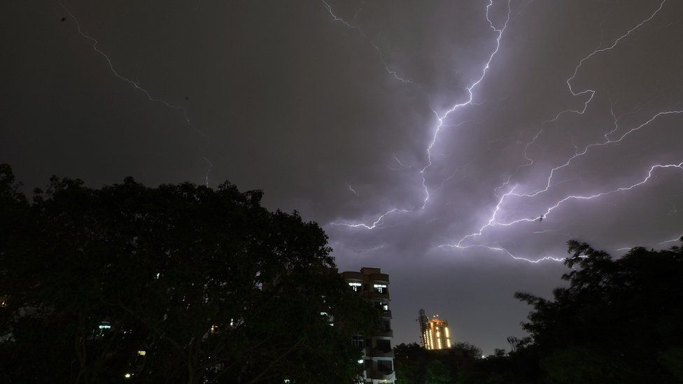 Lightning strikes over residential apartments during a thunderstorm on the outskirts of the Indian capital New Delhi on May 2, 2018