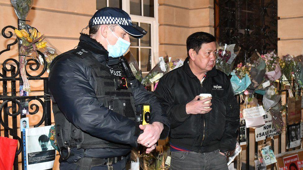 Myanmar ambassador to UK Kyaw Zwar Minn speaks to police officer outside Myanmar's embassy in Mayfair, London