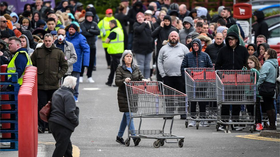 Members of the public queue to get into the Costco store in Glasgow, Scotland before opening on the morning of March 21, 2020, a day after the British government said it would help cover the wages of people hit by the coronavirus outbreak as it tightened restrictions to curb the spread of the disease.