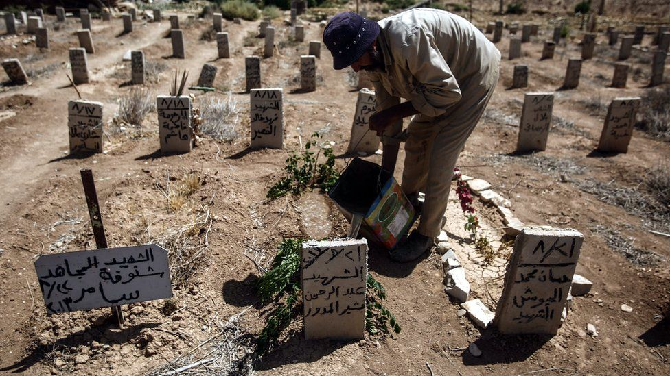 A picture made available on 22 August 2016 showing Abo Ezzo, a worker in the cemetery of Douma, drops some water and put a green branch on the tombs of Abd al-Rahman al-Moudawer, a volunteer who died while helping people in Zamalka during the chemical attack,
