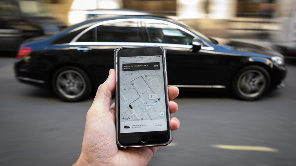 Uber app on a smartphone in front of a car