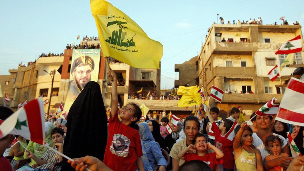 Lebanese children wave Hezbollah and national flags during a ceremony in the Uzai area south of Beirut, 14 July 2007, to mark one year after Hezbollah fired a missile that hit an Israeli navy ship 'Saar 5' two days after the start of the 34-day summer war 14 July 2006.