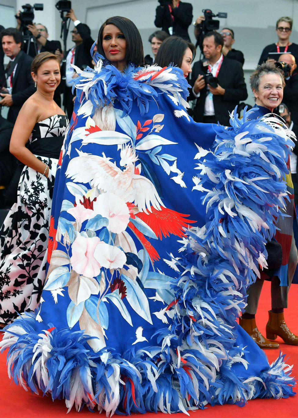 Iman wears a flamboyant dress featuring a red, white and blue pattern and feathers.