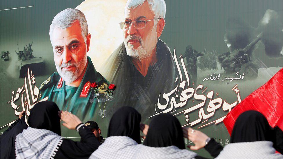 Iraqi women salute a poster showing the late Iranian General Qasem Soleimani and militia leader Abu Mahdi al-Muhandis, who were killed in a US drone strike in Baghdad in January (13 February 2020)
