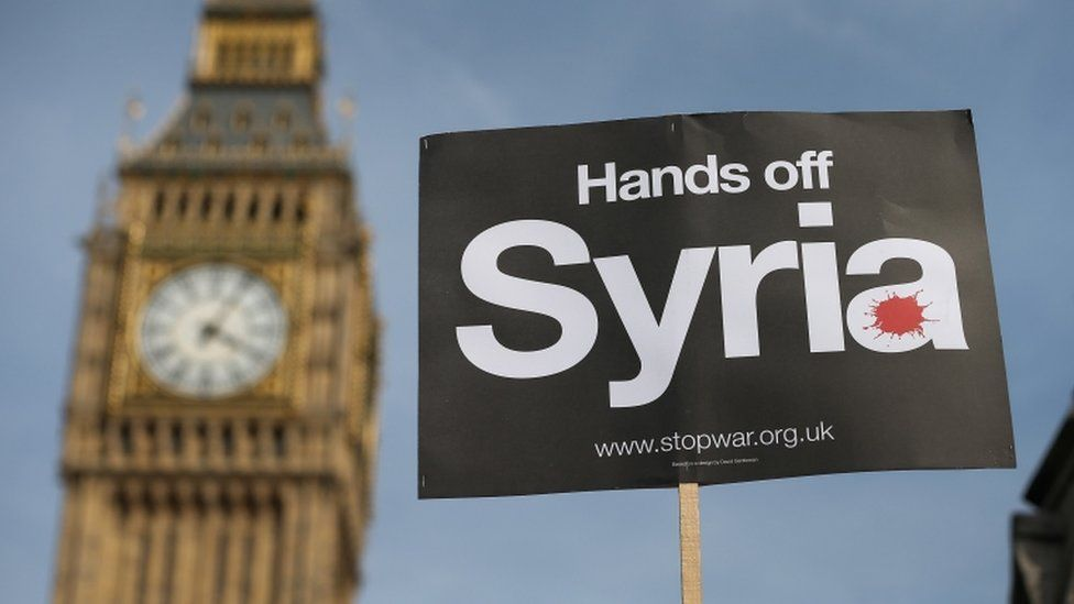 A peace campaigner holds up a placard outside Parliament on 29 August 2013 when MPs rejected plans to bomb Syria