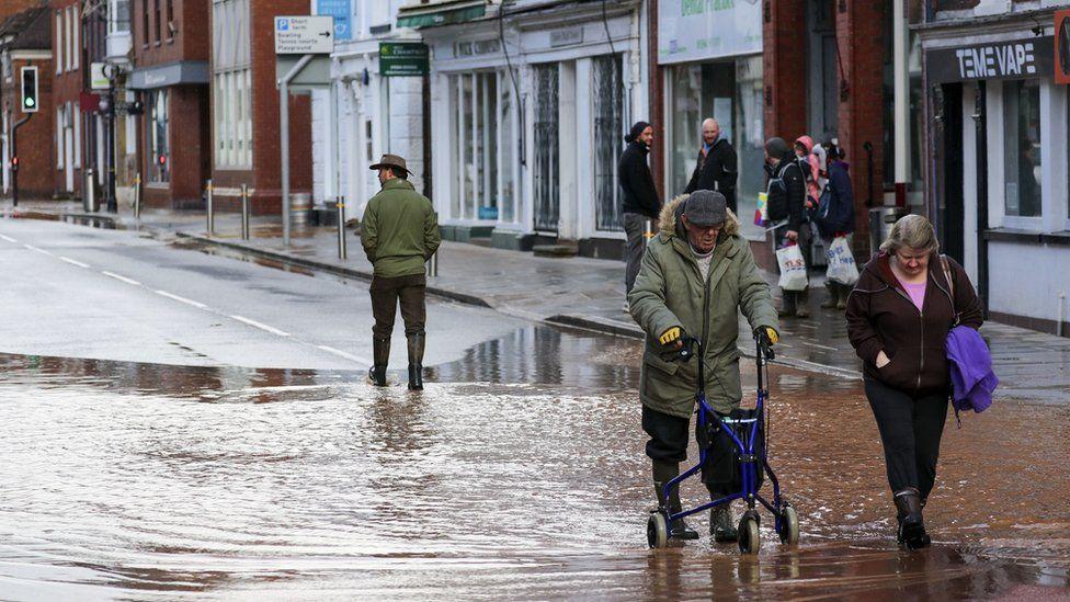 People wade through flood water in Tenbury Wells, Worcestershire