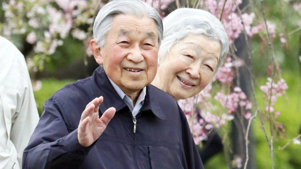 Japan's Emperor Akihito (L) and Empress Michiko walk among cherry blossom in Tokyo (April 2019)