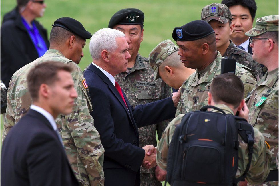US Vice President Mike Pence (centre L) shakes hands with US military officers upon his arrival at army base Camp Bonifas in Paju near the truce village of Panmunjom during a visit to the Demilitarized Zone (DMZ) on the border between North and South Korea on 17 April 2017.