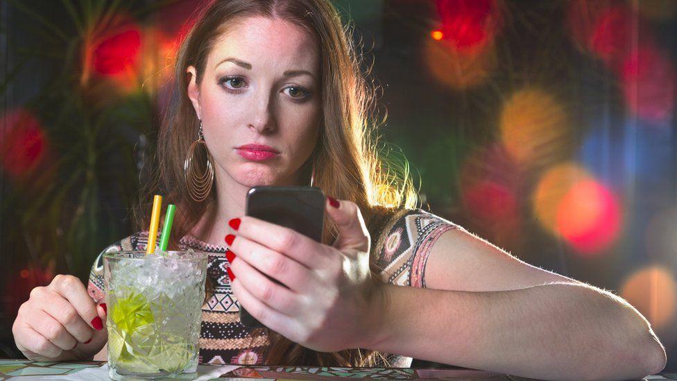 Sad looking woman reading phone