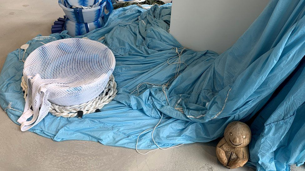 Art installation comprising different objects including basins and blue parachute silk