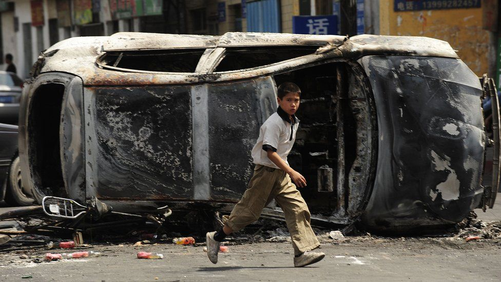 A boy runs in front of the burnt wreck of a car in a street in Urumqi in July 2009