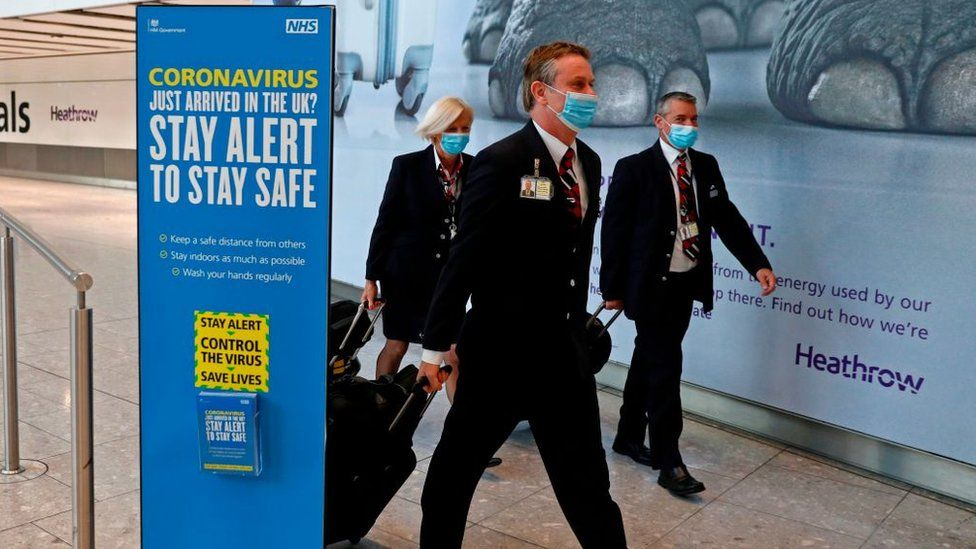 British Airways pilots wearing masks walk through Heathrow Airport