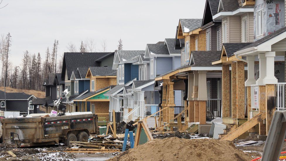 Homes are being rebuilt in Fort McMurray one year after a devastating fire, April 18, 2017 in Fort McMurray, Canada. A few late-season snowflakes flutter over Fort McMurray, their whiteness contrasting against surrounding forests blackened one year ago by the most destructive wildfire in Canadian history