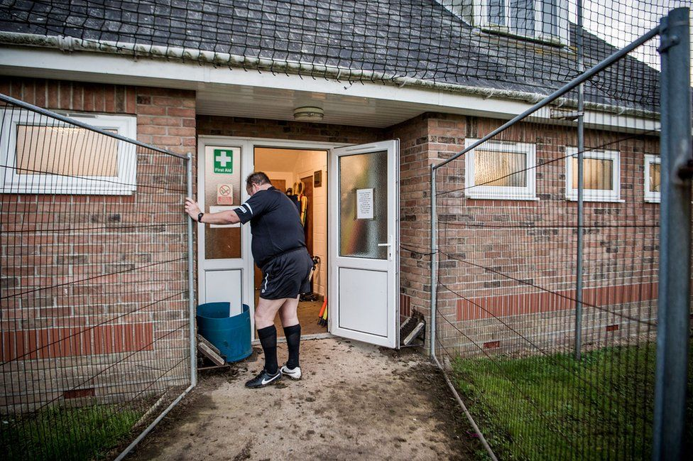 A linesman cleans his boots