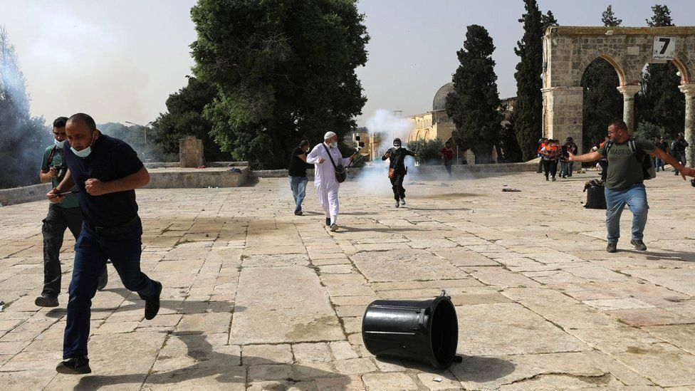 Palestinians run away after Israeli police fire stun grenades during clashes around the al-Aqsa mosque, in occupied East Jerusalem (10 May 2021)