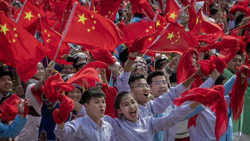 Chinese participants wave the national flag as they in a parade to celebrate the 70th Anniversary of the founding of the People's Republic of China in 1949,