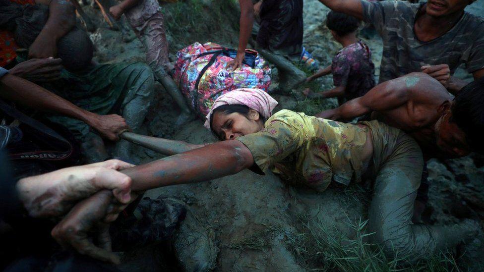 Fotógrafos ayudan a una mujer musulmán rohingya a salir del río Naf,