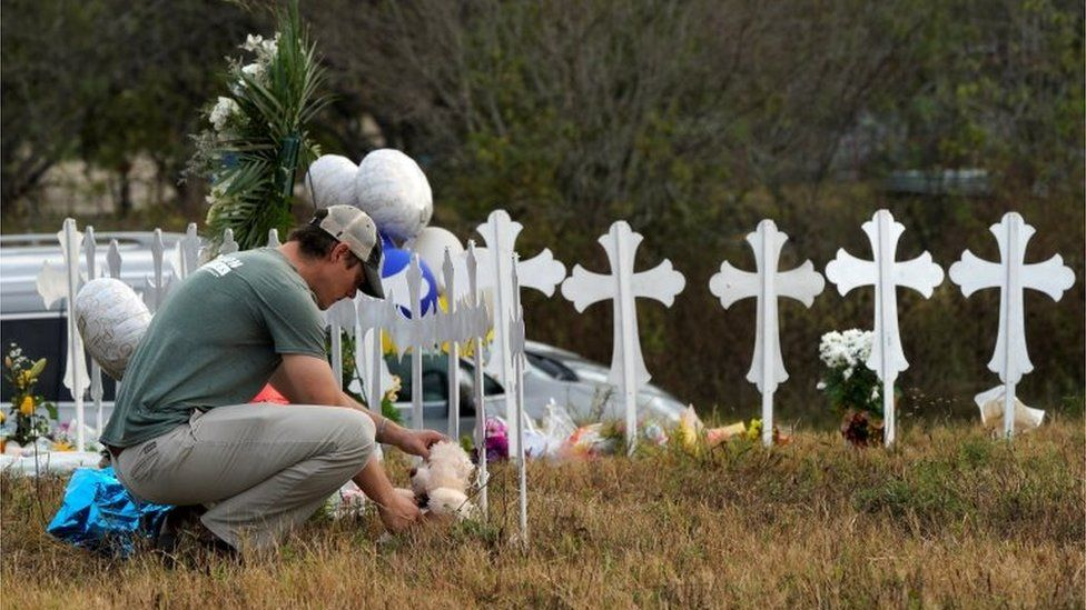 A man places a Teddy bear near a row of memorial crosses in Sutherland Springs, Texas.