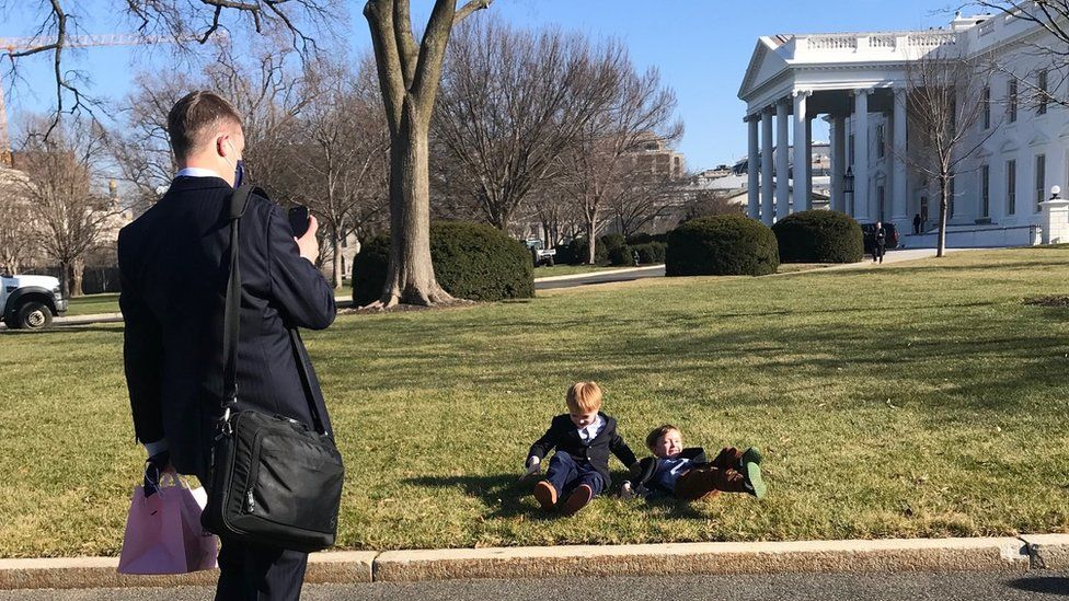 Man taking picture of children on White House lawn
