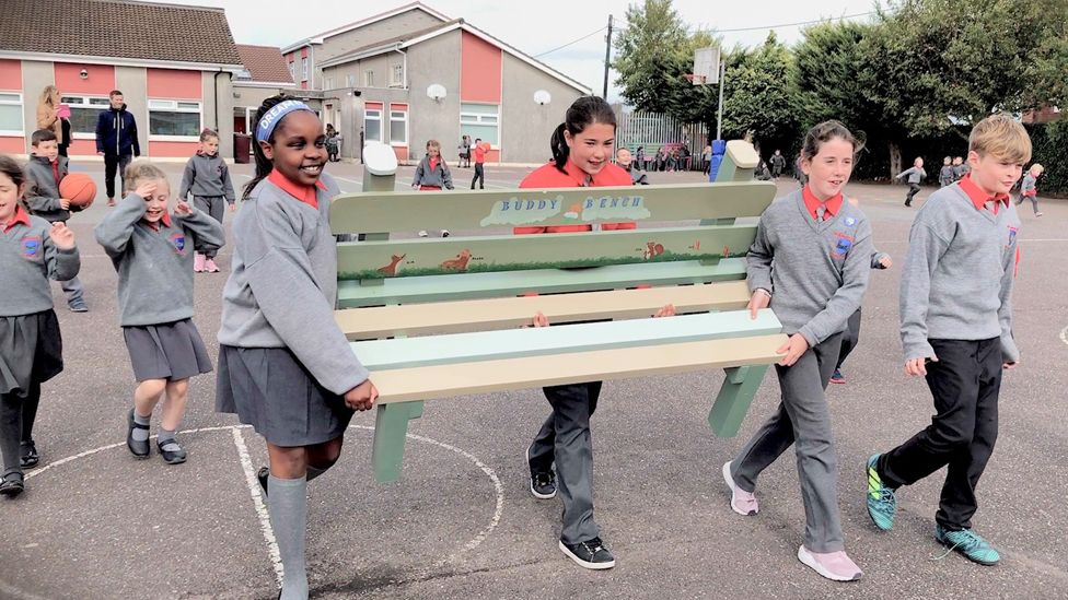 Children carrying a Buddy Bench