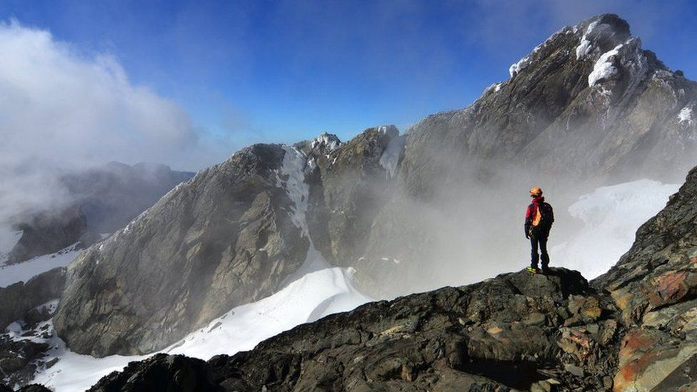 A hiker looking over to the summit of Margherita Peak, Rwenzori.