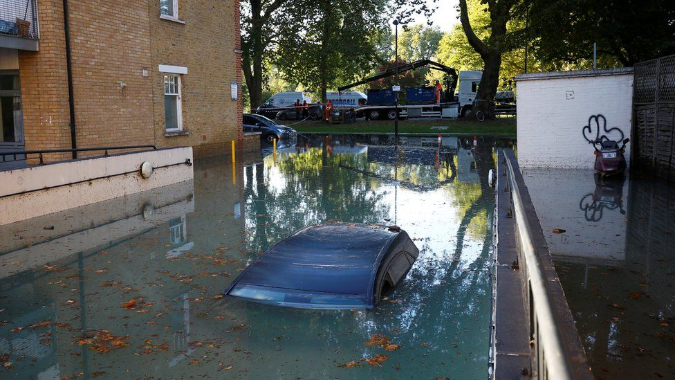 A car is submerged after a water supply pipe burst in the Hackney district of London, 3 October 2018