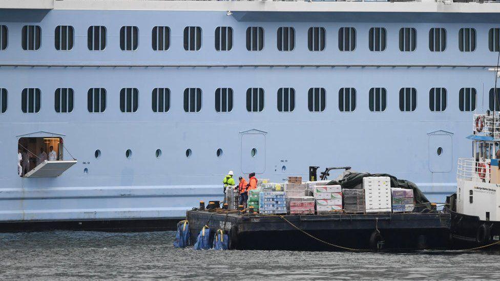 hatch opened on side of cruise ship with supply tug alongside