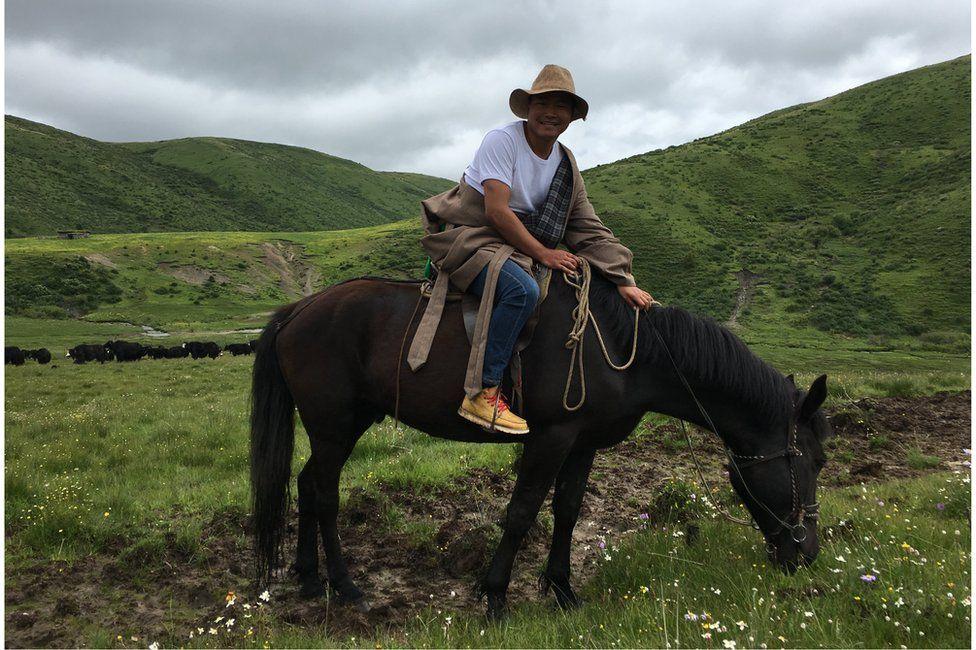 Tshe Bdag Skyabs on his horse amid grass fields