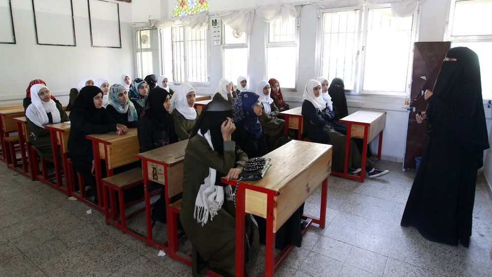 Yemeni girls listen to their teacher at a public school in Sanaa