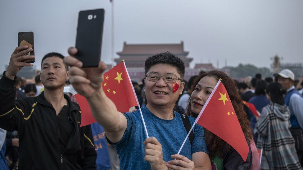 Two people take a selfie in Tiananmen Square