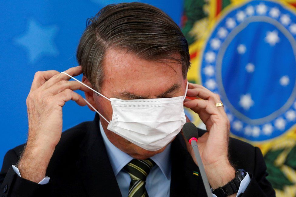 Brazil's President Jair Bolsonaro adjusts his protective face mask