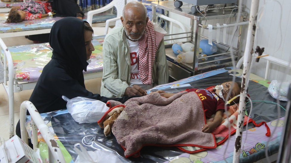 Nawal al-Maghafi sits with Shuaib's grandfather at the boy's bedside