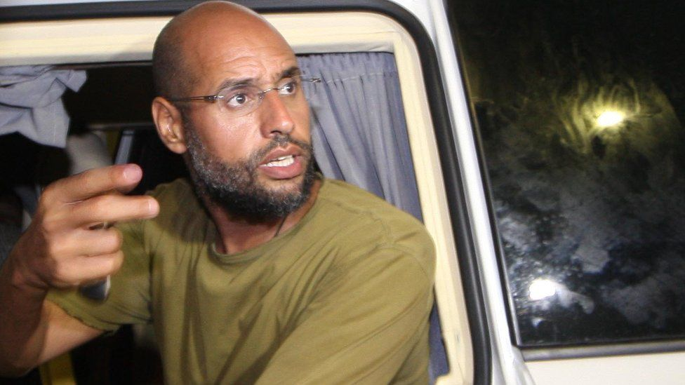 Saif al-Islam Gaddafi appears in front of supporters and journalists at his father's residential complex in the Libyan capital Tripoli in the early hours of 23 August 2011