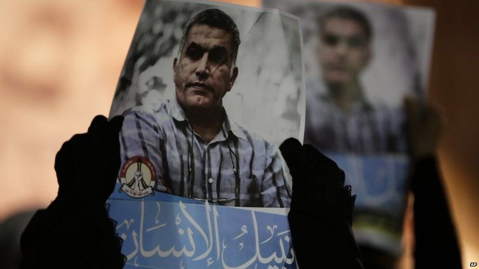 Bahraini anti-government protesters hold up images Nabeel Rajab during a solidarity protest outside his home in Bani Jamra, Bahrain (14 May 2015)