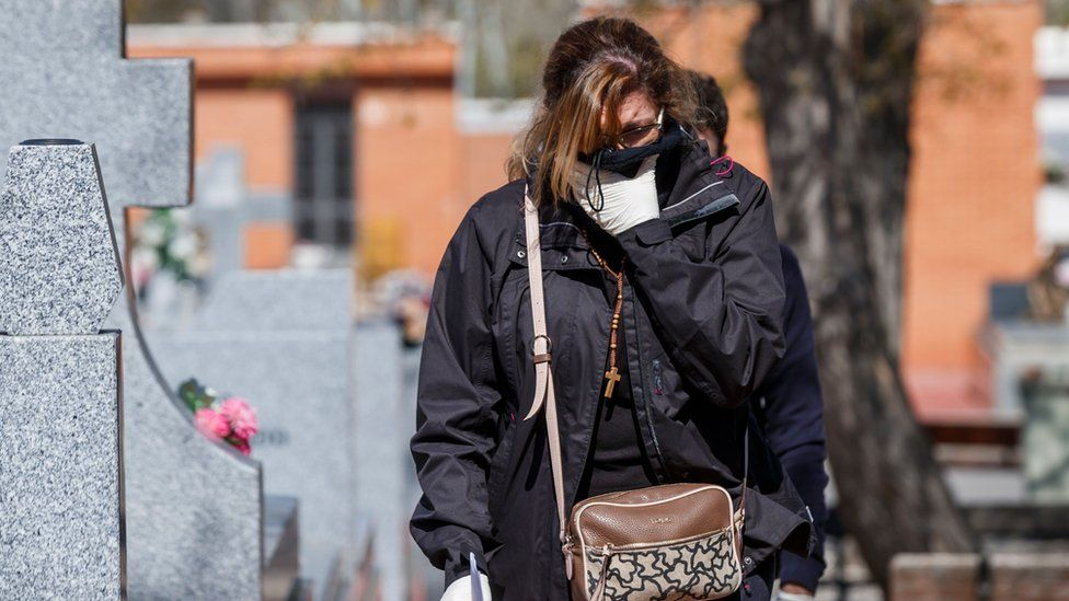 A woman arrives for the burial of a COVID-19 coronavirus victim at the Fuencarral cemetery in Madrid
