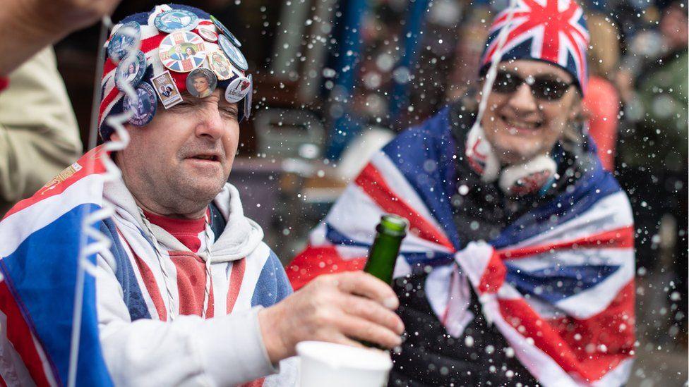 Royal fans wearing union jacks celebrate the announcement outside Windsor Castle