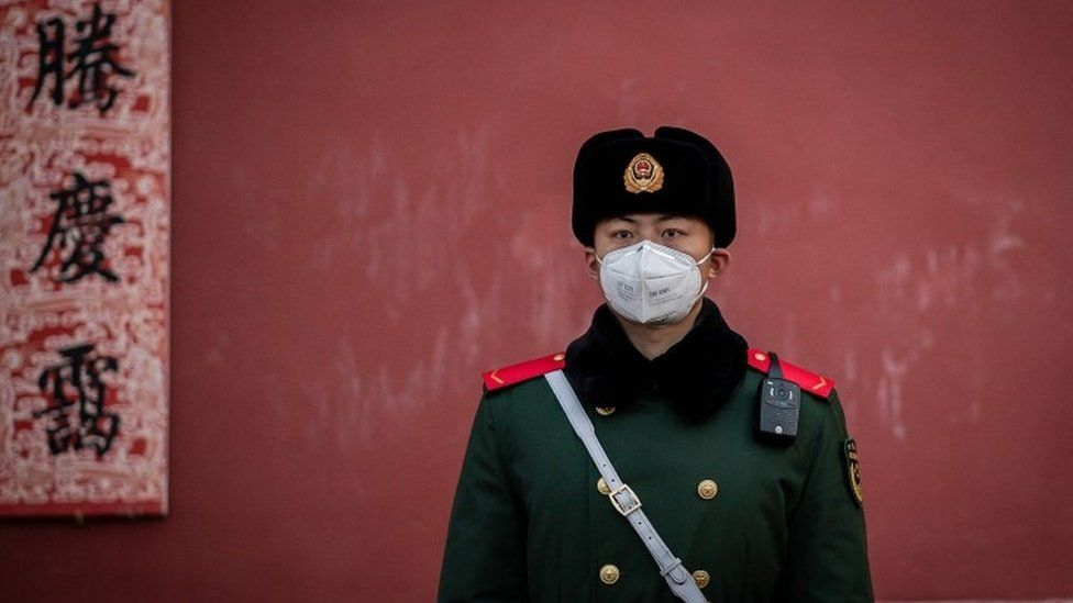 A paramilitary police officer stands guard at the exit of the Forbidden City in Beijing