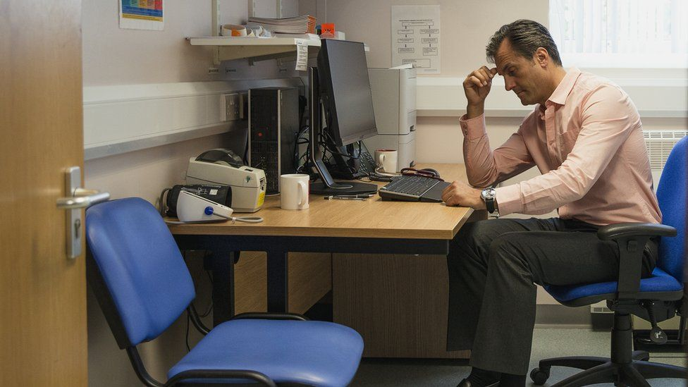 A GP sits at his desk