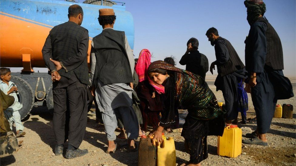 In this photo taken on August 3, 2018, drought-displaced Afghan people fill water containers from a tanker at a camp for internally displaced people in Injil district of Herat province