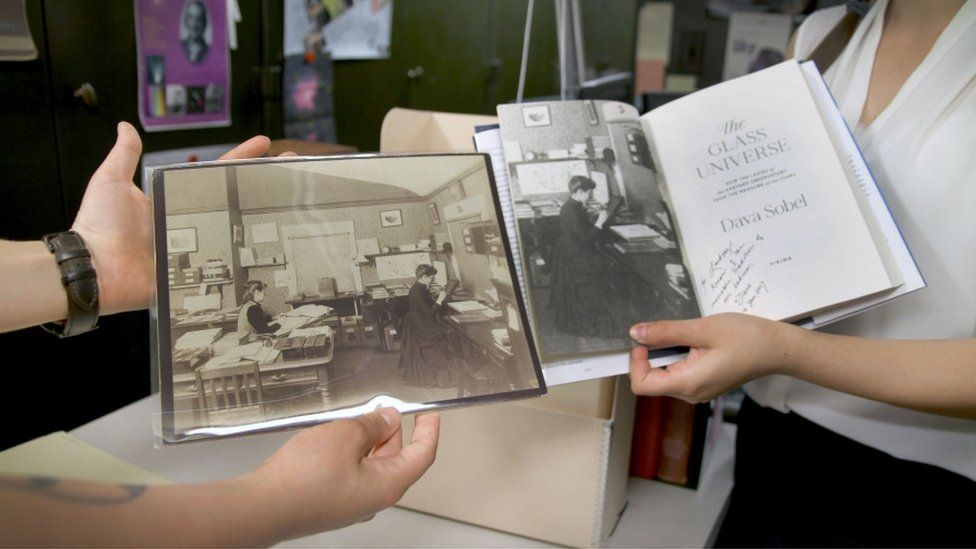 """Bouquin, left, and Smith Zrull, right, hold up an original image of Williamina Fleming posing in the plate stacks in a 1891 photo that was the first photo used in bestselling author Dava Sobell's 2016 book, """"The Glass Universe."""" Smith Zrull says they know the 1891 image is posed because a window is closed and the tool Fleming is using to study a plate only works with window light."""