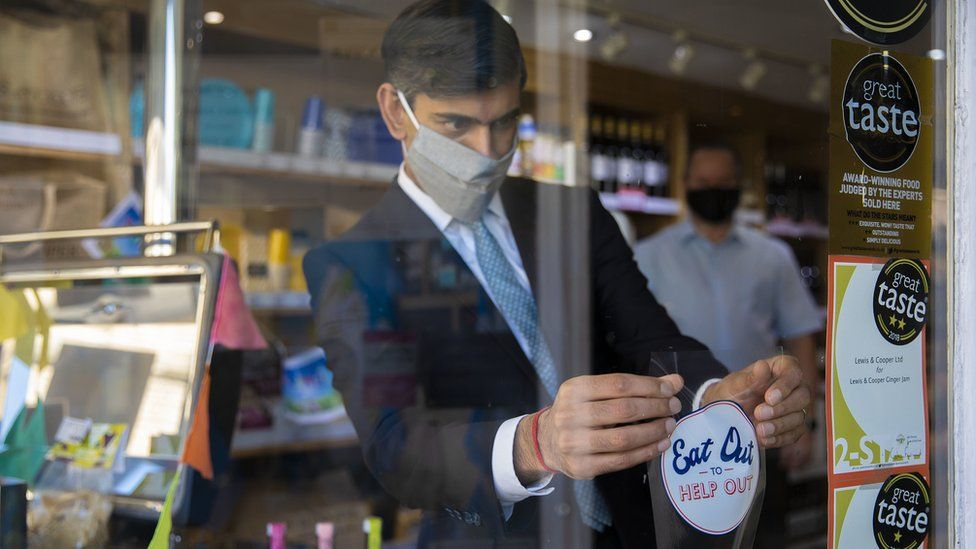 """The Chancellor Rishi Sunak applies an """"eat out to help out"""" sticker in a window"""