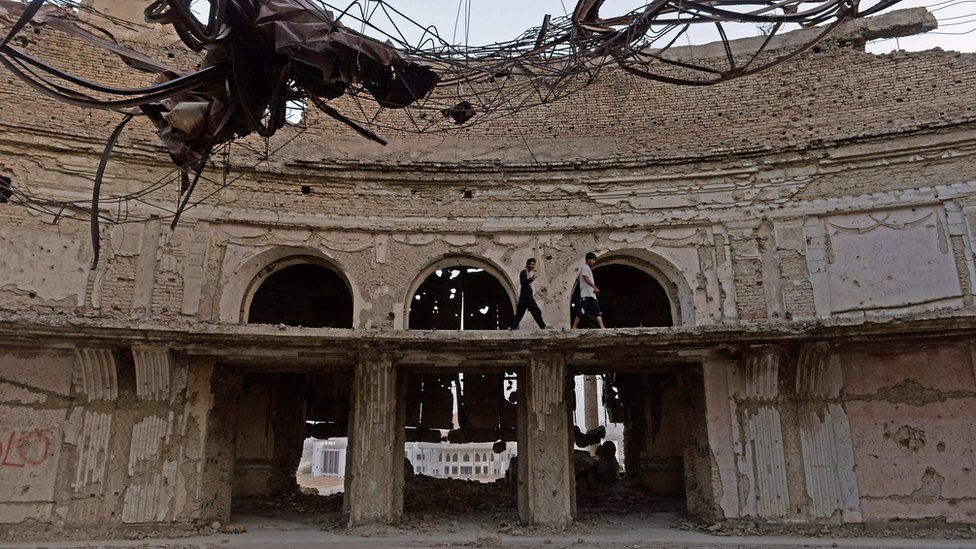 Afghan men walk among the ruins of the Darul Aman Palace in Kabul on 22 August 2014