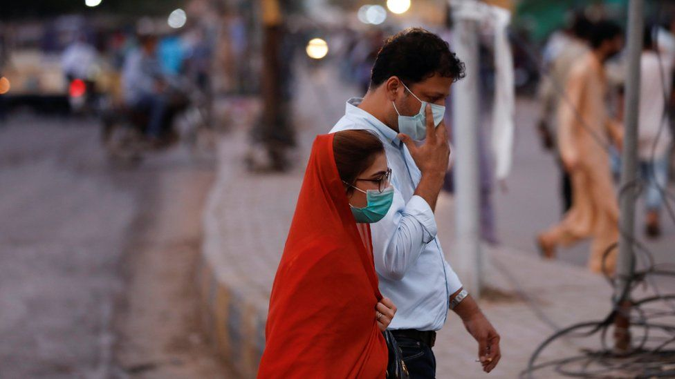 A man and woman wear protective masks while walking along a street after Pakistan lifted lockdown restrictions, as the coronavirus disease (COVID-19) outbreak continues, in Karachi, Pakistan August 18, 2020.
